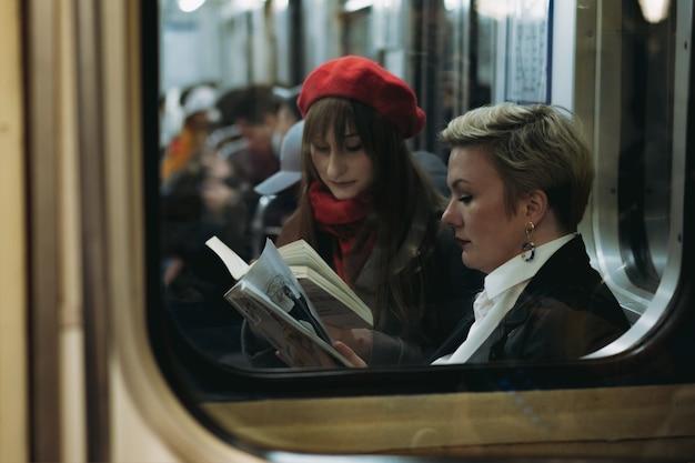 Jovem mulher caucasiana sentada no vagão do metrô e lendo livros