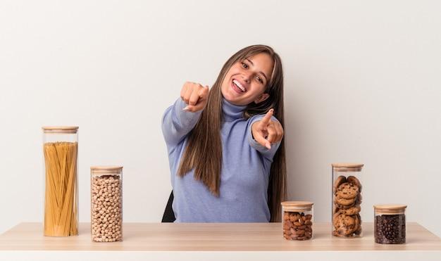 Jovem mulher caucasiana, sentado a uma mesa com o pote de comida isolado em sorrisos alegres de fundo branco, apontando para a frente.