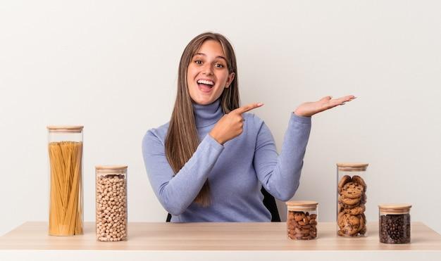 Jovem mulher caucasiana, sentado a uma mesa com um pote de comida isolado no fundo branco, animado, segurando um espaço de cópia na palma da mão.