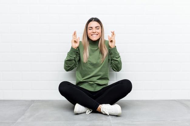 Jovem mulher caucasiana, sentado no chão cruzando os dedos por ter sorte