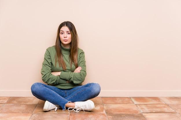 Jovem mulher caucasiana, sentado no chão infeliz olhando na câmera com expressão sarcástica.