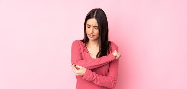 Jovem mulher caucasiana sobre parede isolada com dor no cotovelo