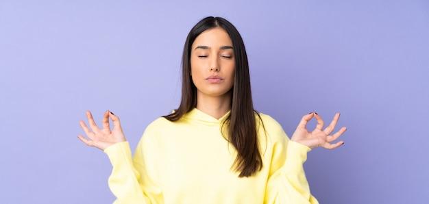 Jovem mulher caucasiana sobre parede isolada em pose de zen