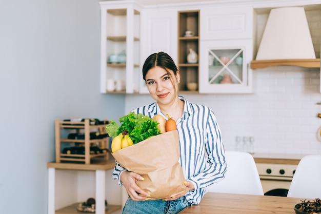 Jovem mulher caucasiana sorridente segura saco de compras eco com legumes frescos e baguete na cozinha moderna.