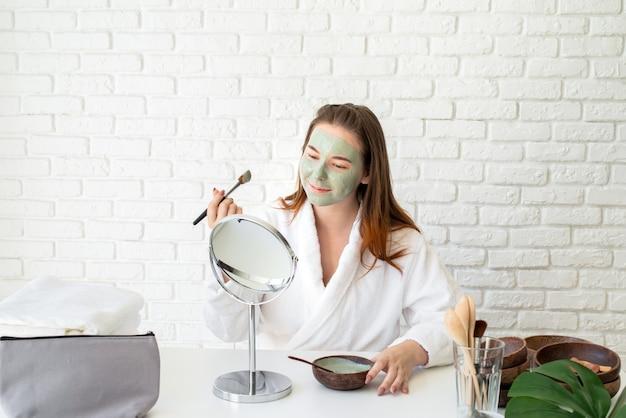 Jovem mulher caucasiana sorridente usando roupão de banho aplicando máscara facial de argila, olhando para o espelho