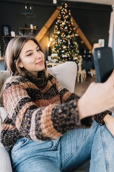 Jovem mulher caucasiana sorridente usando telefone celular, fazendo selfie perto da árvore de natal em casa