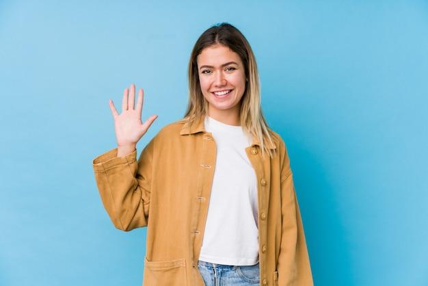 Jovem mulher caucasiana, sorrindo alegre mostrando número cinco com os dedos.