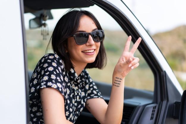 Jovem mulher caucasiana sorrindo e mostrando o sinal da vitória com um rosto alegre em uma van ao ar livre
