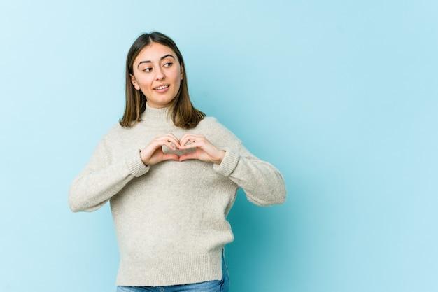 Jovem mulher caucasiana, sorrindo e mostrando uma forma de coração com as mãos.