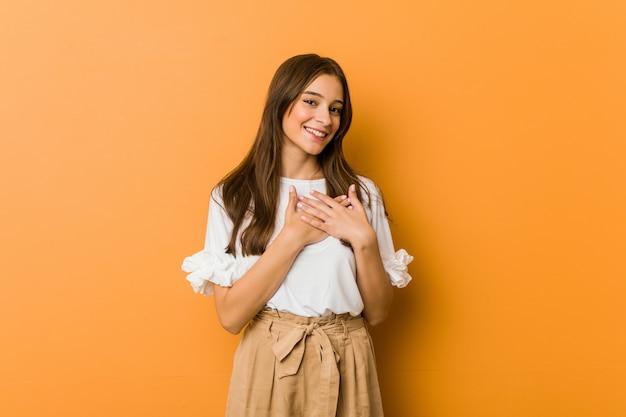 Jovem mulher caucasiana tem expressão amigável, pressionando a palma da mão no peito. conceito de amor