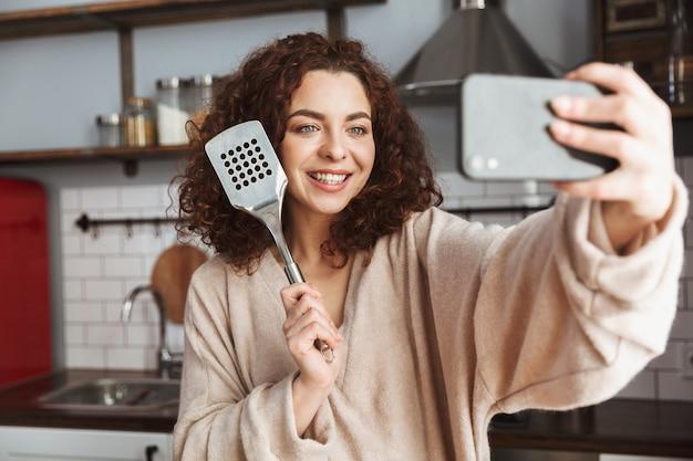 Jovem mulher caucasiana tirando foto de selfie no smartphone enquanto cozinha salada de legumes frescos no interior da cozinha em casa