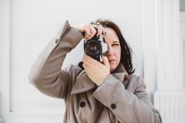Jovem mulher caucasiana, tirando uma foto com sua câmera antiga