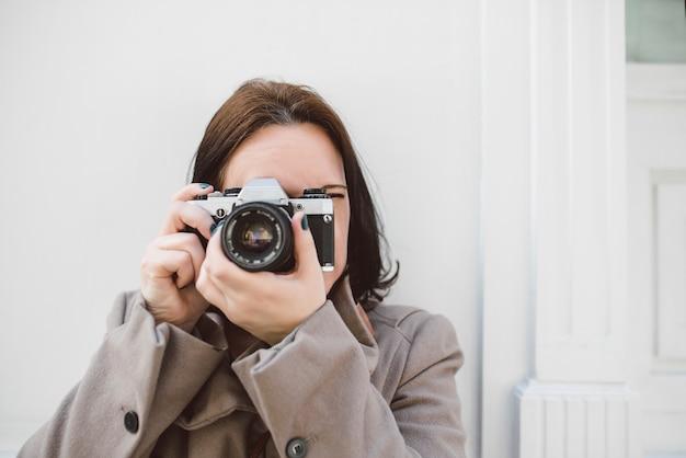 Jovem mulher caucasiana, tirando uma foto com um olho fechado encostado em uma parede branca com sua câmera antiga