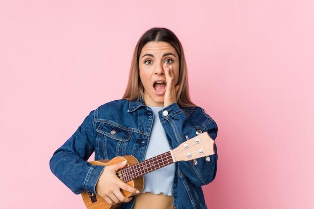 Jovem mulher caucasiana, tocando ukelele gritando animado para a frente.