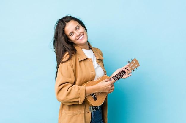 Jovem mulher caucasiana tocando ukelele isolada em azul