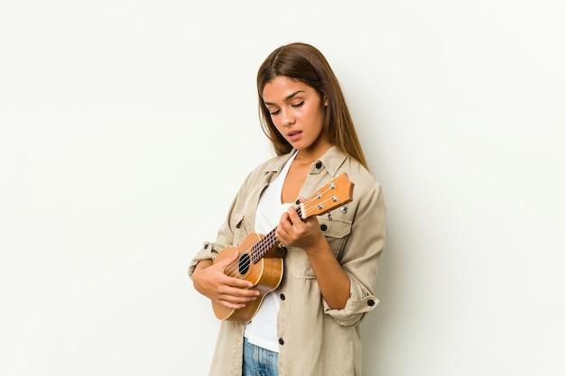 Jovem mulher caucasiana tocando ukelele isolada
