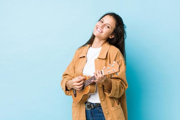 Jovem mulher caucasiana, tocando ukelele isolado em uma parede azul