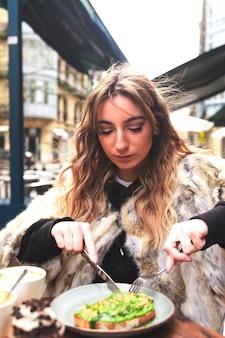Jovem mulher caucasiana, tomando café da manhã em um terraço, comendo uma torrada de abacate.