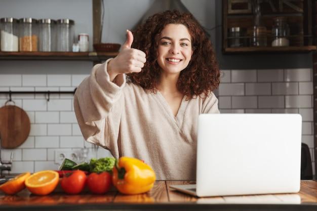 Jovem mulher caucasiana usando laptop enquanto cozinha salada de legumes fresca no interior da cozinha em casa