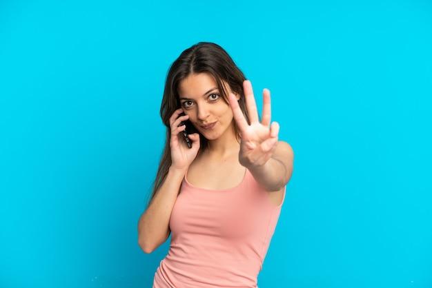 Jovem mulher caucasiana usando telefone celular isolado em um fundo azul feliz e contando três com os dedos