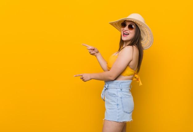 Jovem mulher caucasiana, usando um chapéu de palha, verão olhar animado apontando com o dedo indicador fora.