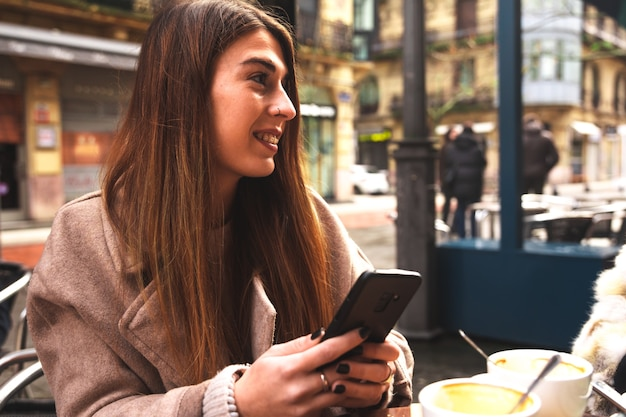 Jovem mulher caucasiana usando um telefone celular enquanto toma o café da manhã em um terraço em uma manhã de inverno