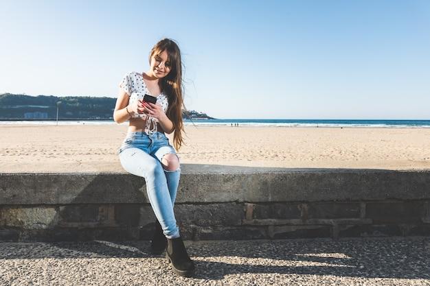 Jovem mulher caucasiana, usando um telefone celular sentado na lateral de um calçadão da praia, em hendaia, país basco.