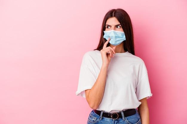 Jovem mulher caucasiana, usando uma máscara para vírus em rosa, olhando de soslaio com expressão duvidosa e cética.
