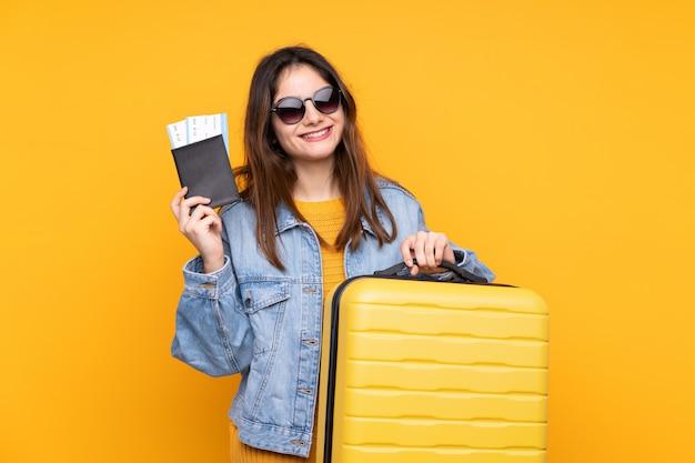 Jovem mulher caucasiana vai viajar sobre parede isolada