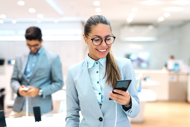 Jovem mulher caucasiana, vestida de terno, experimentando o novo telefone inteligente. interior da loja de tecnologia.