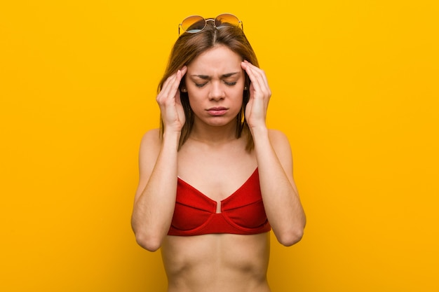 Jovem mulher caucasiana, vestindo biquíni e sunglassesuching seus templos e tendo dor de cabeça.