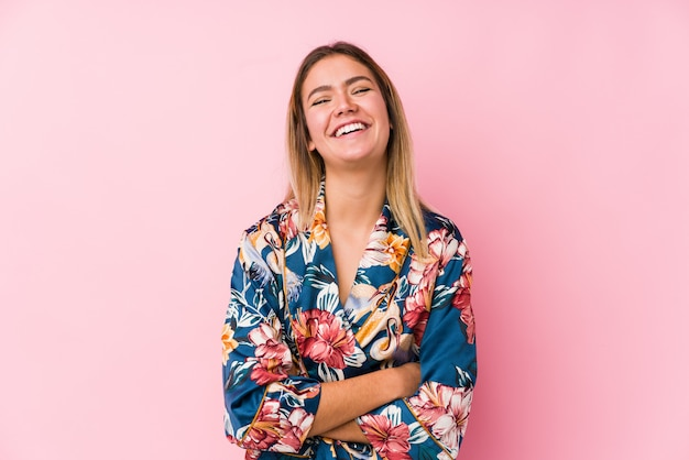 Jovem mulher caucasiana, vestindo pijama, rindo e se divertindo