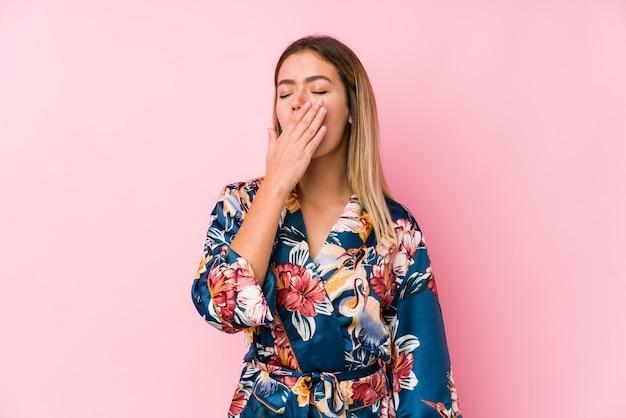 Jovem mulher caucasiana, vestindo pijamas bocejando, mostrando um gesto cansado, cobrindo a boca com a mão.