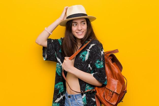 Jovem mulher caucasiana, vestindo um biquíni e chapéu