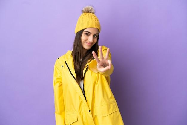 Jovem mulher caucasiana, vestindo um casaco à prova de chuva isolado em um fundo roxo, feliz e contando três com os dedos