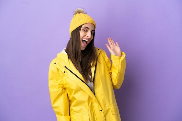 Jovem mulher caucasiana, vestindo um casaco à prova de chuva isolado no fundo roxo, saudando com a mão com expressão feliz