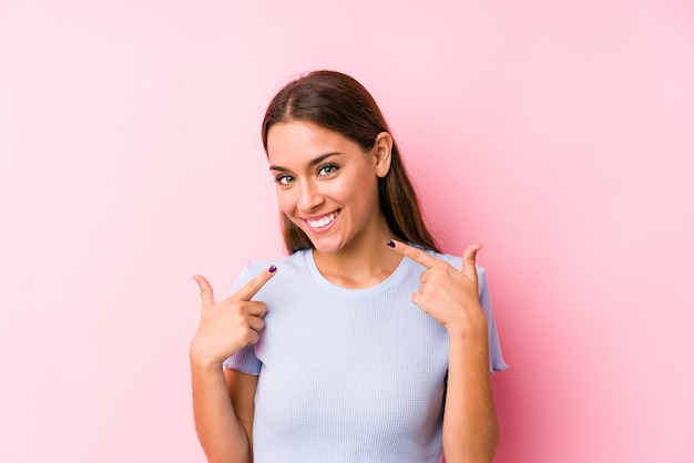 Jovem mulher caucasiana, vestindo um esqui roupas isolados sorrisos, apontando os dedos na boca.