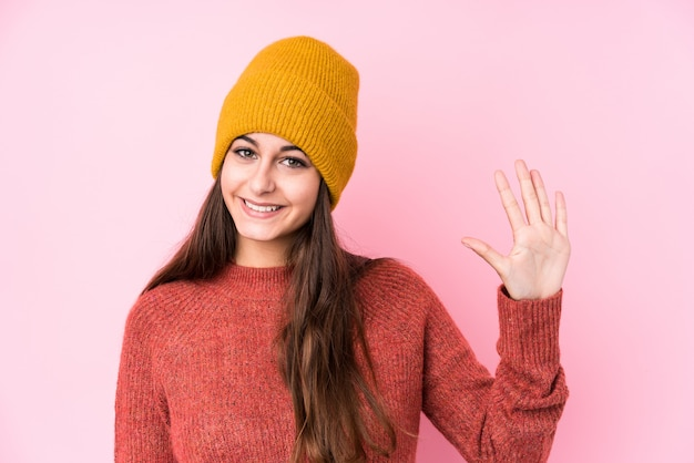 Jovem mulher caucasiana, vestindo um gorro de lã, sorrindo alegre mostrando o número cinco com os dedos.