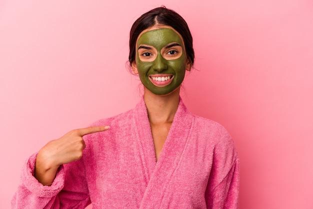 Jovem mulher caucasiana vestindo um roupão de banho e máscara facial isolada em um fundo rosa pessoa apontando com a mão para um espaço de cópia de camisa, orgulhosa e confiante