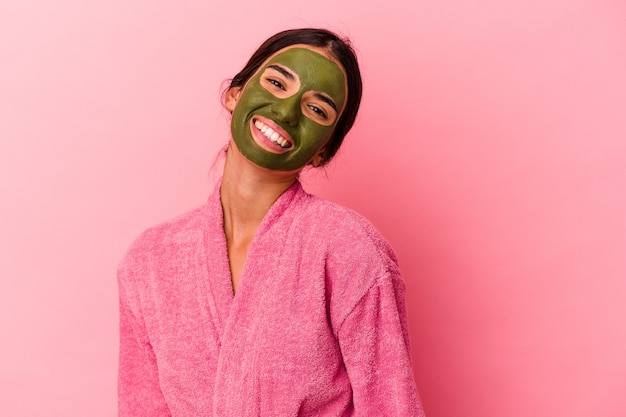 Jovem mulher caucasiana vestindo um roupão de banho e máscara facial isolada em um fundo rosa