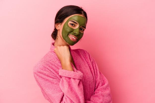 Jovem mulher caucasiana, vestindo um roupão de banho e máscara facial isolada em um fundo rosa