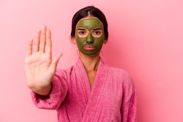 Jovem mulher caucasiana, vestindo um roupão de banho e máscara facial, isolada no fundo rosa, em pé com a mão estendida, mostrando o sinal de pare, impedindo você.