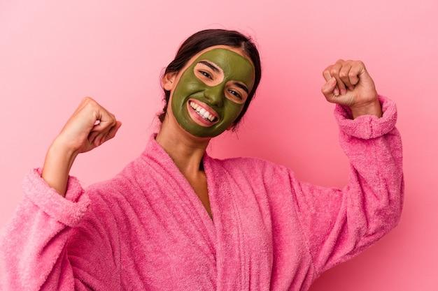 Jovem mulher caucasiana, vestindo um roupão de banho e máscara facial, isolada no fundo rosa, levantando o punho após uma vitória, o conceito de vencedor.