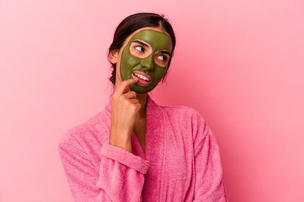 Jovem mulher caucasiana, vestindo um roupão de banho e uma máscara facial isolada no fundo rosa, relaxou pensando em algo olhando para um espaço de cópia.