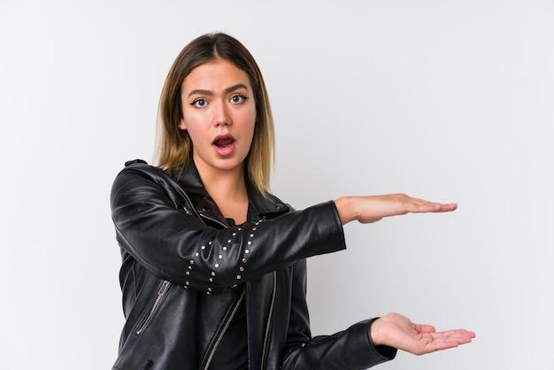 Jovem mulher caucasiana, vestindo uma jaqueta de couro preta chocada e espantada, segurando um espaço de cópia entre as mãos.