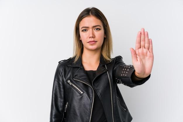 Jovem mulher caucasiana, vestindo uma jaqueta de couro preta em pé com a mão estendida, mostrando o sinal de stop, impedindo-o.