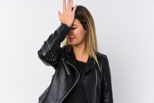 Jovem mulher caucasiana, vestindo uma jaqueta de couro preta, esquecendo de algo, batendo na testa com a palma da mão e fechando os olhos.