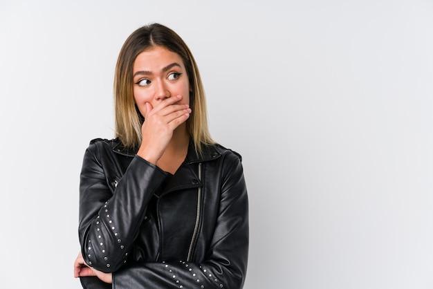 Jovem mulher caucasiana, vestindo uma jaqueta de couro preta, pensativo, olhando para um espaço de cópia, cobrindo a boca com a mão.