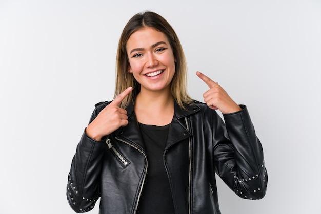 Jovem mulher caucasiana, vestindo uma jaqueta de couro preta sorrindo