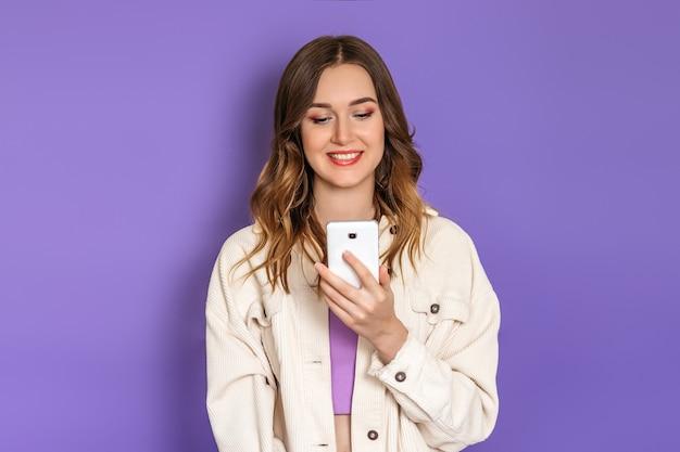 Jovem mulher caucasiana, vestindo uma jaqueta de veludo cotelê bege, olhando para a tela do telefone e sorrindo, isolada em um fundo lilás